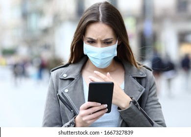 Front view portrait of a scared girl wearing protective mask avoiding contagion reading news on her smart phone on a city street