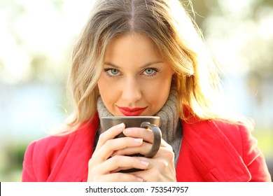 Front view portrait of a sensual woman with blue eyes looking at camera holding a coffee cup outdoors in a park