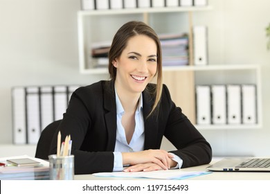Front view portrait of a smiley office worker posing looking at camera