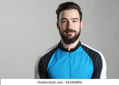 Front view portrait of smiling happy cyclist wearing cycling jersey t-shirt over gray studio background.
