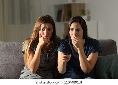 Front view portrait of two worried friends watching tv in the night sitting on a couch in the living room at home