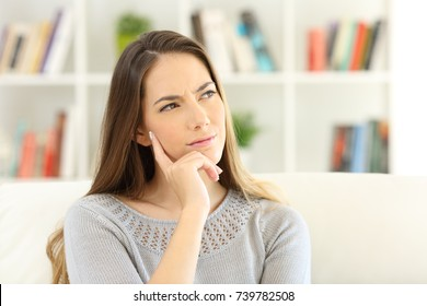 Front view portrait of a woman wondering sitting on a sofa at home