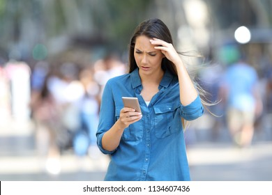Front view portrait of a worried woman checking smart phone messages walking on the street