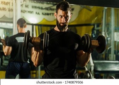 Front view portrait of young caucasian man male athlete bodybuilder training at the gym workout using dumbbells biceps curls wearing black shirt dark hair and beard standing weight lifting