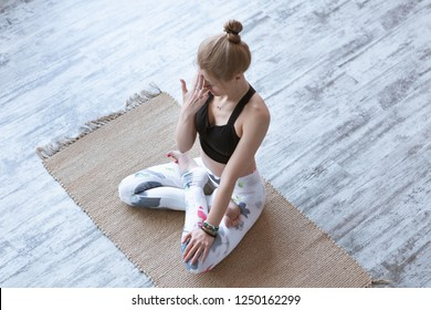 Front view portrait of young woman working out, resting after doing yoga exercises, using nadi shodhana pranayama technique ana breath
