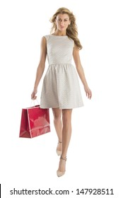 Front view portrait of young woman walking with shopping bag isolated over white background