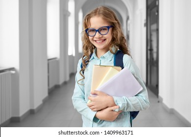 Front view of pretty blonde school girl wearing blue shirt and eyeglasses holding many colorful notes and books. Clever teen girl smiling at camera, standing on corridor of international school.