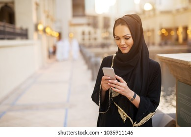 Front view of a pretty young girl smiling while looking at her phone.