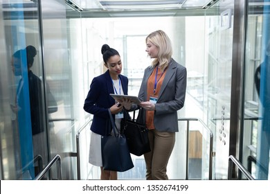 Front view of pretty young multi-ethnic businesswomen discussing over digital tablet in modern office elevator