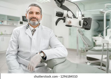 Front view of professional male dentist in white doctor coat and protective gloves sitting near dental chair and equipment, looking at camera and smiling. Bearded man posing during working process.