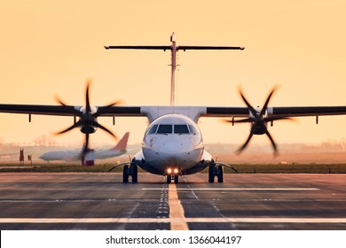 Front view of propeller airplane taxiing to runway for take off. Traffic at airpot at sunset.