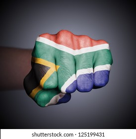 Front view of punching fist on gray background, flag of South Africa