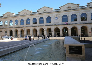 Front view of the façade of the Nîmes railway station, in Gard department, Boulevard Sergent Triaire, France. November, 2, 2018. White stone walls with arcades and windows. Blue sky in background.