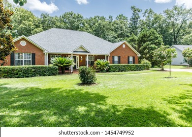 Front view of red brick house in the suburbs with a spacious lawn and trees with lots of curb appeal