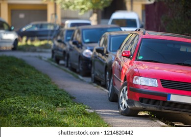 Front view of red car parked partly on sidewalk on background of long row of different vehicles along roadside on sunny autumn day. Transportation, modern city lifestyle, parking problem concept.