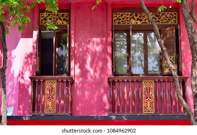 Front view of red exterior of traditional vintage Singapore Straits Chinese Peranakan shop house or shophouse with antique shutters and soft evening shadows