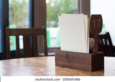 front view of restaurant table setting with ketchup wood box and white blank menu pages