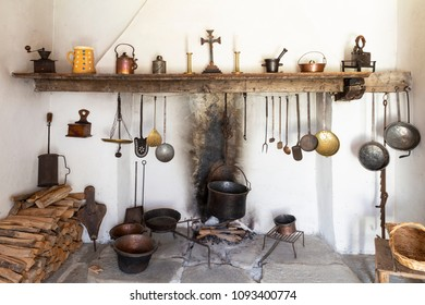 Front view of a retro style rustic kitchen with open fireplace, cooking tools, pans, and various other kitchen equipment