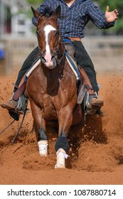 The front view of a rider sliding the horse in the sand.