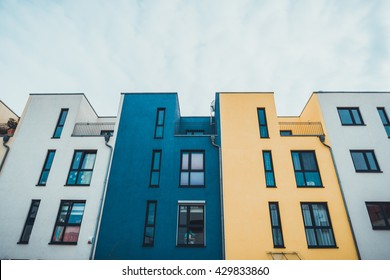 Front view of a row of colorful luxury townhouses with an identical design painted blue , yellow and white viewed looking up from below