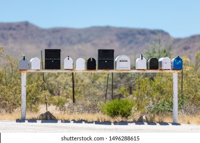 Front view of a row of traditional american letterboxes in a backcountry setting, against an out of focus background with distant mountains