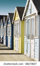 Front view of a row of wooden beach huts with wooden terraces located in Christchurch Hampshire UK. Huts painted in pale blue and yellow colours.