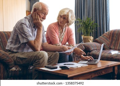 Front view of sad Caucasian senior couple discussing bill while sitting on vintage sofa at retirement home. Senior woman is using laptop.