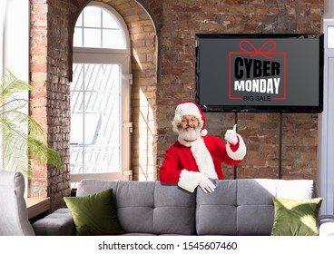 Front view of Santa pointing of screen with cyber monday lettering in modern home or office. Copyspace. Black friday, sales, finance, advertising, money, finance, purchases. New Year, Christmas.