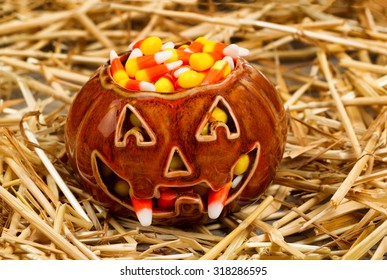 Front view of scary pumpkin with fangs filled with candy corn on straw. Halloween concept.