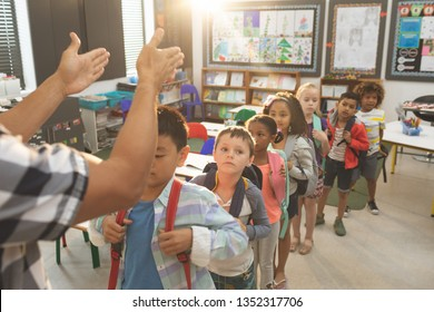 Front view of school kids standing and forming a queue in classroom at school