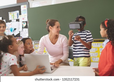 Front view of schoolboy using virtual reality headset at school in classroom at school