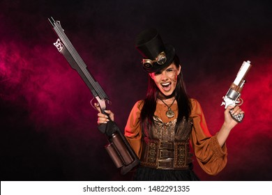 front view of screaming steampunk woman holding gun and pistol in pink smoke on black
