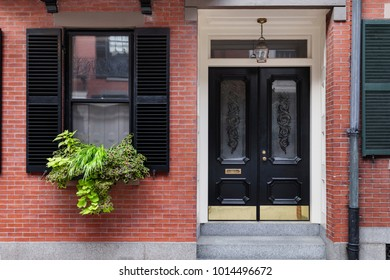 Front view of a secured house with black shutters and a potted plant along the windowsill