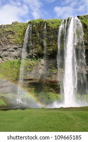 front view of Seljalandsfoss waterfall with rainbow in Iceland