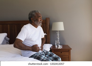 Front view of a senior African American man suffering from stomach ache in bedroom at home