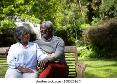 Front view of senior African American couple in the garden, sitting on a bench, embracing and talking. Family enjoying time at home, lifestyle concept
