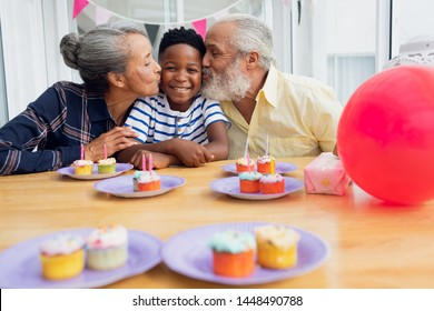 Front view of senior African-American man and woman kissing their grandson for his birthday party. Authentic Senior Retired Life Concept