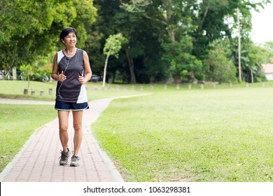 Front view of senior Asian woman jogging through park