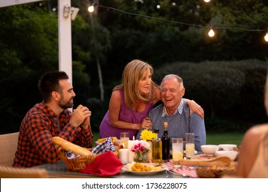 Front view of a senior Caucasian couple embracing, at a dinner table for a family celebration meal, the woman is standing beside the man, while their adult son sits smiling at them