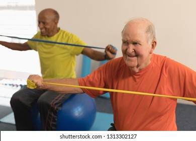 Front view of senior man exercising with resistance band in fitness studio