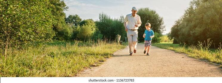 Front view of senior man with hat and happy child running on a nature path. Two different generations concept.