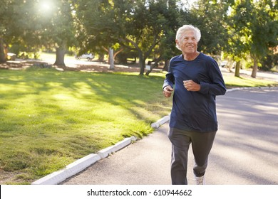 Front View Of Senior Man Jogging Through Park