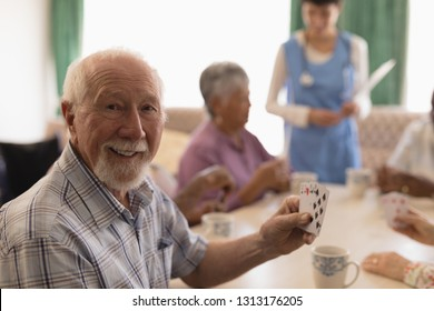 Front view of senior man playing cards with senior people and female doctor on behind in living room at home