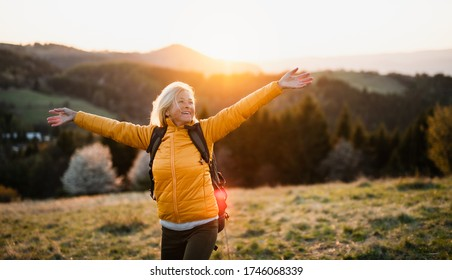 Front view of senior woman hiker standing outdoors in nature at sunset. - Shutterstock ID 1746068339
