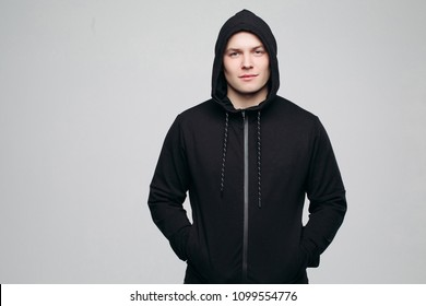 Front view of serious athletic man in black shirt with  hood on head, posing, holding hands in pockets. Handsome and stylish male looking at camera. Concept of male fashion and look.