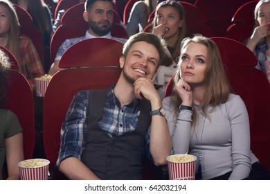 Front view of serious blonde woman and smiling brunet man watching movie in modern cinema hall, looking at screen. Two best friends spending time together, thinking, dreaming when watching film.