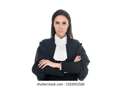Front view of serious judge in judicial robe standing with folded arms isolated on white