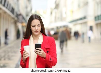 Vista frontal de una mujer seria con un abrigo rojo usando un smartphone con café para llevar caminando por la calle en invierno