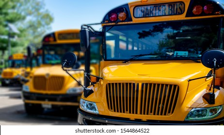 Front view of shiny yellow school bus parked at event within a row of other buses that are blurred in the background on a clear sky day