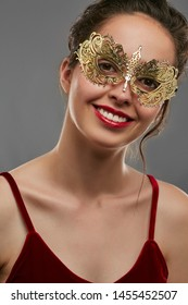 Front view shot of girl with dark hair, wearing wine red crop top. The smiling lady is tilting head, wearing golden Venetian carnival mask with fancy perforation. Vintage women's carnival accessory.